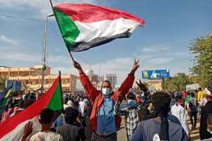 A Sudanese protester waves the national flag during a rally outside the army complex in the capital Khartoum. By OZAN KOSE (AFP)