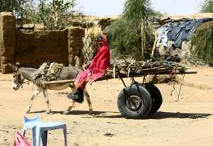A Sudanese refugee sits on a cart at a UN refugee camp in the city of Nyala, in South Darfur, on January 9, 2017