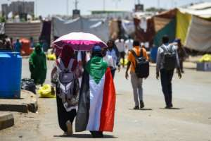 A Sudanese woman walks draped in a national flag with another protester beneath an umbrella at the protest outside the army headquarters in the capital Khartoum. By Mohamed el-Shahed (AFP)