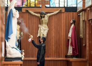 A sacristan wearing a face mask disinfects the religious statues inside the Sagrada Familia Church in Mexico City.  By ALFREDO ESTRELLA (AFP)