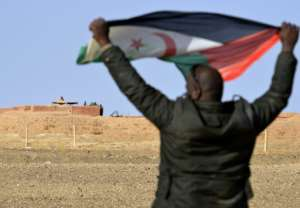 A Sahrawi, in February 2017, holds aloft a Polisario flag under the watchful eyes of Moroccan soldiers guarding an observation post on the 2,700-kilometre long wall (1,700 miles) that Rabat built to defend its control of the disputed Western Sahara.  By STRINGER (AFP/File)