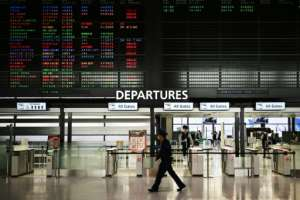 A security guard walks past a signboard showing cancelled flights at the international departures area of Narita International Airport in Narita, Japan -- Prime Minister Shinzo Abe said the country's hospitals face a