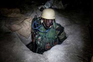 A Senegalese soldier emerges from a bunker at a captured rebel base in Blaze Forest in Casamance.  By JOHN WESSELS (AFP)