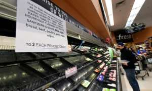 A sign announces a two-item limit for certain items as people shop for food in Monterey Park, California.  By Frederic J. BROWN (AFP)