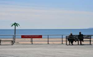 A sign reading 'Keep This Far Apart', remind speople of social distancing, is seen on the Coney Island boardwalk in New York City.  By Angela Weiss (AFP)