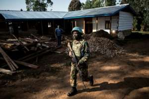A soldier (pictured March 9, 2019) from the UN Organisation Stabilisation Mission patrols outside an Ebola Treatment Centre in Butembo, as rebel fighters in the region have dramatically complicated the response to the disease. By JOHN WESSELS (AFP/File)