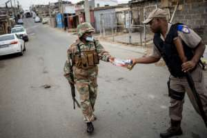 A South African soldier (left) hands over cigarettes he seized from a small shop to a policeman. The tobacco ban is still in force.  By Michele Spatari (AFP/File)