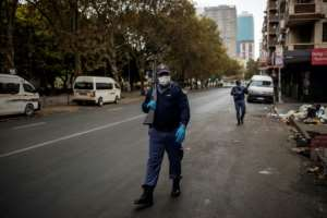 A South African policeman patrols as he holds a pump rifle in Hillbrow, Johannesburg.  By Michele Spatari (AFP/File)