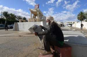 A Tunisian man reads a newspaper in front of a statue to Mohamed Bouazizi, the man whose protest kickstarted revolution a decade ago; Tunisia today remains beset by challenges.  By FETHI BELAID (AFP)