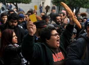 A Tunisian woman holds up a yellow card and a loaf of bread during a protest against price hikes and austerity measures in the capital Tunis on January 12, 2018