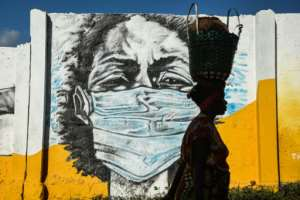A Tanzanian woman walks in front of a mural painted by the Wachata artists group to raise awareness about avoiding the spread of coronavirus. Magufuli has claimed prayer saved the country from Covid-19.  By Ericky BONIPHACE (AFP/File)
