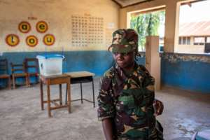 A Tanzanian security officer waits to cast her ballot in early voting.  By Patrick Meinhardt (AFP)