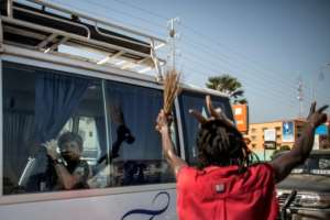 A tourist looks from inside a bus at a supporter of the newly elected Gambian president Adama Barrow, celebrating in the streets of Senegambia, on December 2, 2016
