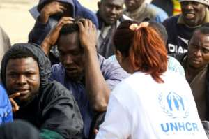 A UNHCR worker tends to African migrants in Libya (pictured March 2018), where the UN refugee agency says reliable sources indicate that smugglers and traffickers pretend they work with that and other UN organisations to target refugees.  By MAHMUD TURKIA (AFP/File)