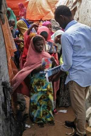 A university student Abdirashid Abdullahi checks notebooks.  By Mohamed ABDIWAHAB (AFP)