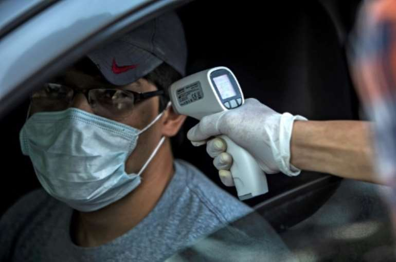 A university student checks the temperature of a driver as a precautionary measure against the spread of coronavirus in Managua. By INTI OCON (AFP)