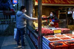 A vendor and customer wearing facemasks as a preventive measure against the novel coronavirus interact at a fruit and vegetable store in Beijing.  By GREG BAKER (AFP)