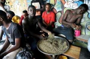 A vendor cuts marijuana for sale in Lagos.  By PIUS UTOMI EKPEI (AFP)
