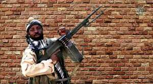 A video grab shows Boko Haram factional leader Abubakar Shekau holding a heavy machine gun.  By Handout (BOKO HARAM/AFP/File)
