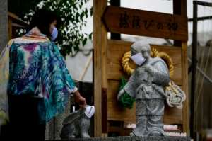 A visitor wearing a face mask points at masked statues at Yasaka Shrine in Kyoto, Japan.  By Philip FONG (AFP)