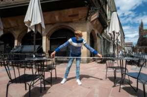 A waiter measures the distance between tables at a Strasbourg restaurant, as France eases its virus measures.  By PATRICK HERTZOG (AFP)