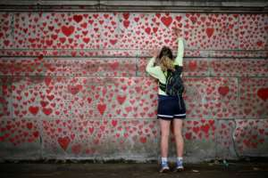 A woman draws on the National Covid Memorial Wall in London.  By Tolga Akmen (AFP)
