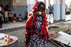 A woman eats at an emergency foodbank in Beira, Mozambique.  By WIKUS DE WET (AFP)