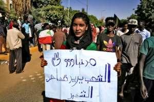 A woman holds up an Arabic-language sign demanding