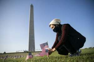 A woman places a flag at a memorial on the National Mall in Washington fo the more than 200,000 people in the United States who have died of Covid-19.  By Alex Edelman (AFP)