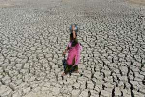 A woman searching for water walks on the parched bed of Chandola Lake, near the Indian city of Ahmedabad. A severe drought struck the region in 2016.  By SAM PANTHAKY (AFP/File)