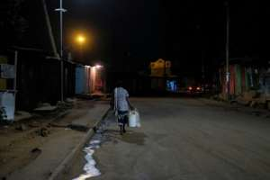 A woman walks home through empty streets after the 7:00 pm curfew having closed her stall late in Kibera.  By Kabir Dhanji (AFP)