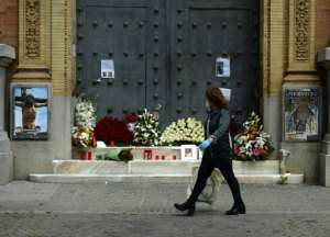 A woman walks past a church in Seville, adorned with flowers and candles left by the faithful after Easter processions were cancelled.  By CRISTINA QUICLER (AFP)