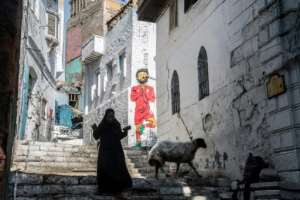 A woman walks past a mural of Egyptian footballer Mohamed Salah in Cairo on June 17, 2019, four days ahead of the African Cup of Nations debut (CAN).  By Khaled DESOUKI (AFP)