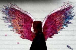 A woman wearing a face mask amid concerns over COVID-19 walks past a graffiti of wings in Tokyo.  By Behrouz MEHRI (AFP)