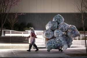 A woman wearing a face mask and a plastic bag pulls a cart loaded with bags of recyclables through the streets of Lower Manhattan.  By Johannes EISELE (AFP)