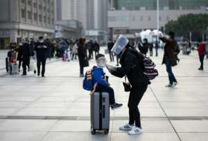 A woman wearing a face mask adjusts her child's mask as they arrive at Wuhan's Hankou rail station to take one of the first trains to leave the Chinese city since a ban on outbound travel was lifted.  By NOEL CELIS (AFP)