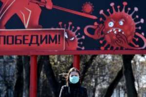 A woman wearing a face mask walks past a sign depicting a virus in Minsk.  By Sergei GAPON (AFP)