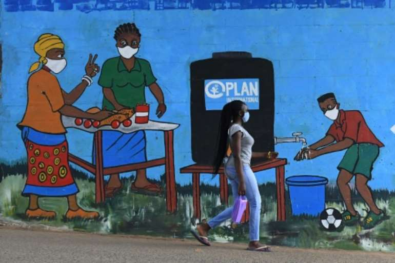 A woman with a face mask walks past graffiti that promotes hand washing and wearing face masks in Nairobi.  By Simon MAINA (AFP/File)