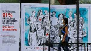 A woman with her baby walks past a street art poster created by the French artist Combo for the International Committee of the Red Cross in Paris.  By THOMAS COEX (AFP/File)