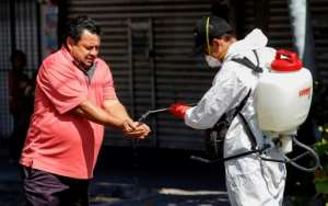 A worker wearing a protective suit sprays disinfectant on a man's hands during a campaign to sanitize public spaces in Guadalajara, Mexico.  By ULISES RUIZ (AFP)