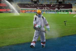 A worker disinfects the pitch at half time during the Rio de Janeiro state championship football final match between Flamengo and Fluminense at Maracana stadium, Rio de Janeiro, Brazil on July 15, 2020.  By CARL DE SOUZA (AFP)