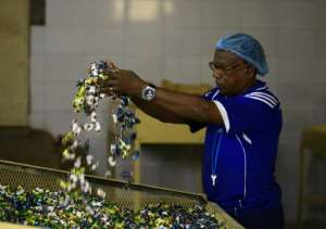 A worker hands sweets at a food and drinks factory owned by Sudanese businessman Samir Gasim, in the capital Khartoum on September 20, 2018.  By ASHRAF SHAZLY (AFP)