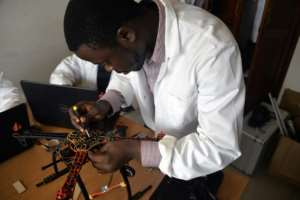 A young engineer works on making a drone entirely built in Cameroon at the Will & Brothers company premises in Douala.  By Reinnier KAZE (AFP)