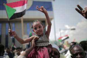 A young Sudanese girl waves the national flag in Khartoum as people celebrate the signing of the Constitutional Declaration after close to eight months of protests.  By Jean Marc MOJON (AFP)