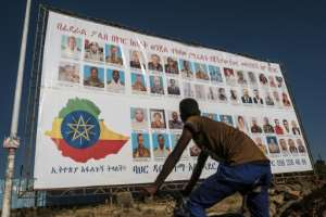 A youngster in Bahir Dar, the capital of Amhara region, stands in front of a wanted sign showing members of the Tigray People's Liberation Front (TPLF), who are being sought for alleged treason.  By EDUARDO SOTERAS (AFP)