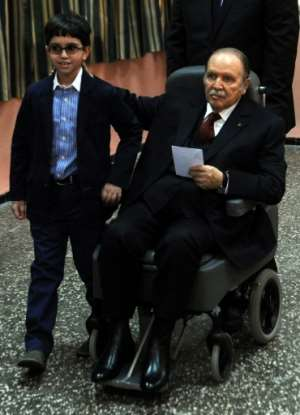 Abdelaziz Bouteflika is pushed in a wheelchair next to his nephew before casting his ballot at a polling station in Algiers while running for re-election on April 17, 2014. By FAROUK BATICHE (AFP/File)