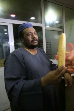 Adel Abdelrahman is one of many Sudanese citizens who complain bread remains too expensive, despite the price falling back from a January peak of three pounds per loaf to one pound per loaf.  By ASHRAF SHAZLY (AFP)
