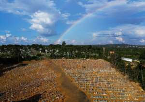 Aerial view of the burial site reserved for victims of the Covid pandemic with a rainbow in the sky at the Nossa Senhora Aparecida cemetery in Manaus, in the Amazon forest in Brazil.  By MICHAEL DANTAS (AFP)