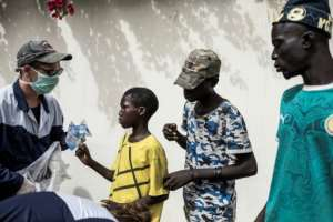 Aid: A worker from Village Pilote hands out water and sandwiches to street children.  By JOHN WESSELS (AFP)