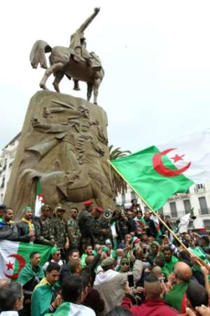 Algerian protesters wave national flags and chant slogans.  By - (AFP)